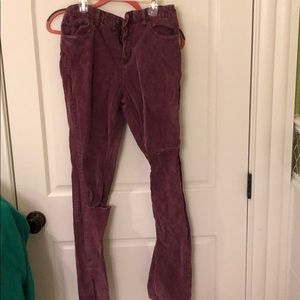 Cranberry corduroy pants with slits in knees.